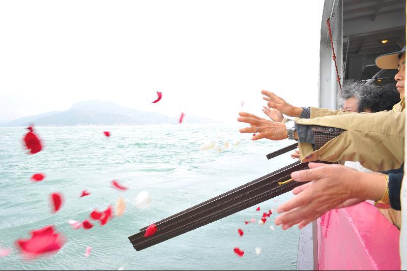 家屬親友撒放鮮花瓣進大海,讓花香陪伴先人骨灰回歸自然。